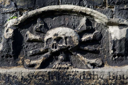 A skull and crossbones carving on a gravestone headstone in a cemetery