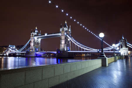 View of Tower Bridge at night from the Thames Path in London  photo