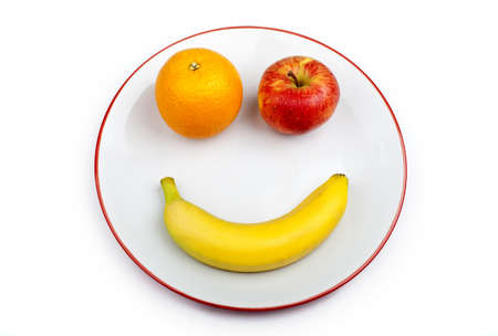 Three different pieces of fruit making up a smiling face on a plate over a white background.