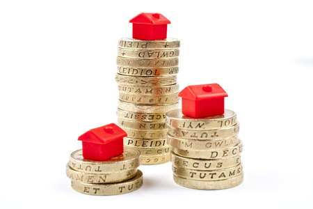 stacked up: �1 Coins Stacked up in three piles.  Saving for a Home. Stock Photo