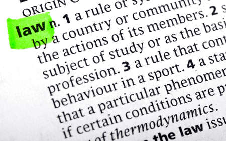 defining: The definition of LAW highlighted in a dictionary. Stock Photo
