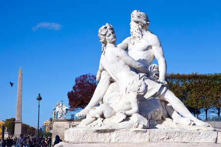 A statue in Tuileries Garden in Paris.  The obelisk in Place de la Concorde can be seen in the distance.