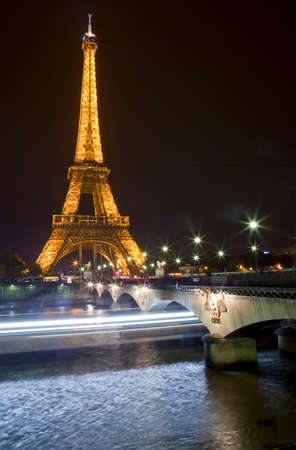 PARIS, FRANCE - NOV 2ND 2013: The Eiffel Tower and light trails of boats travelling underneath the Pont dlena in Paris on November 2nd 2013.