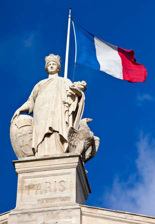 Statue and French flag above the main entrance of Gare du Nord Station in Paris. photo
