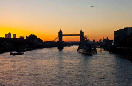 The beautiful sunrise behind Tower Bridge in London   HMS Belfast, City Hall and the skyscrapers in Docklands are also visible  photo