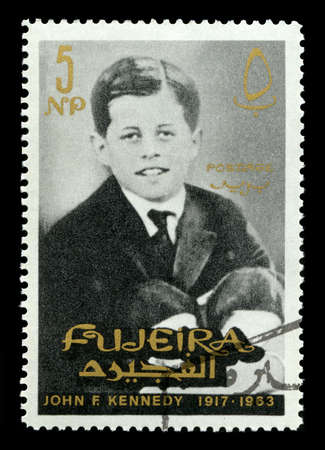 FUJEIRA, CIRCA 1965: A vintage Postage Stamp from Fujeira featuring a young portrait of former President of the United States John F. Kennedy, circa 1965.