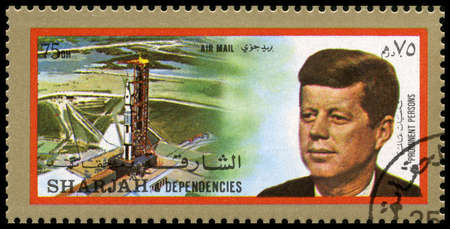 jfk: SHARJAH, CIRCA 1972: A Postage Stamp from Sharjah showing a portrait of former President of the United States John F. Kennedy and an Apollo launchpad, circa 1972.