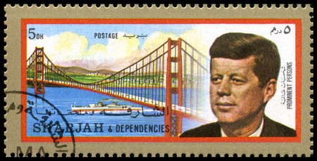 dependencies: SHARJAH, CIRCA 1972: A Postage Stamp from Sharjah showing a portrait of former President of the United States John F. Kennedy and the Golden Gate Bridge, circa 1972. Editorial