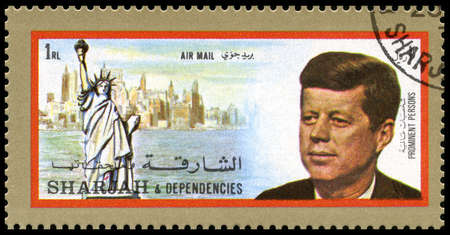 SHARJAH, CIRCA 1972: A Postage Stamp from Sharjah showing a portrait of former President of the United States John F. Kennedy and the Statue of Liberty in New York, circa 1972. 報道画像