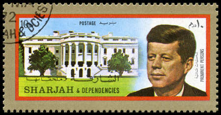 dependencies: SHARJAH, CIRCA 1972: A Postage Stamp from Sharjah showing a portrait of former President of the United States John F. Kennedy and the White House, circa 1972.