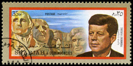 dependencies: SHARJAH, CIRCA 1972: A Postage Stamp from Sharjah showing a portrait of former President of the United States John F. Kennedy and Mount Rushmore, circa 1972.