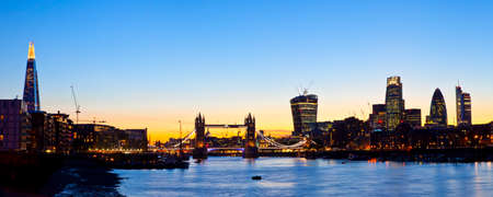 A panoramic view of the beautiful London skyline at dusk.  The view takes in sights including the Shard, Tower Bridge, St Pauls Cathedral, 20 Fenchurch Street (Walkie Talkie Building), 122 Leadenhall Street (The Cheesegrater), The Gherkin, and Heron Towe