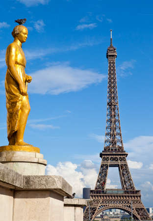 One of the golden statues at Museum Palais de Chaillot, at\ the Trocadero in Paris. The Eiffel Tower is in the distance.\
