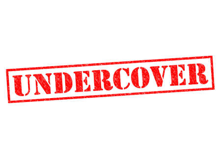 undercover: UNDERCOVER red Rubber Stamp over a wite background.