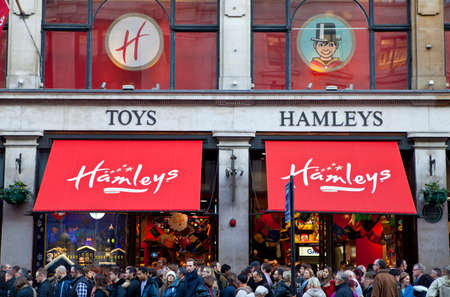 toy shop: LONDON, UK - NOVEMBER 29TH 2014: Crowds of shoppers flood past and into Hamleys Toy Shop on Regent Street in London, on 29th November 2014.  Founded in 1760, Hamleys is the oldest toy shop in the world and one of the worlds most famous retailers of toys.