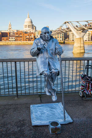 millennium bridge: LONDON, UNITED KINGDOM - 17TH FEBRUARY 2015: A street Entertainer in London with St. Pauls Cathedral and the Millennium Bridge in the background on 17th February 2015.