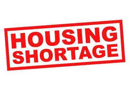 afford: HOUSING SHORTAGE red Rubber Stamp over a white background. Stock Photo