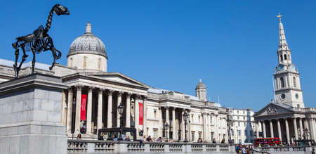 plinth: LONDON, UK - APRIL 7TH 2015: A panoramic view taking in the sights of the National Gallery, St Martin in the Fields church and the Fourth Plinth in Trafalgar Square, London on 7th April 2015.