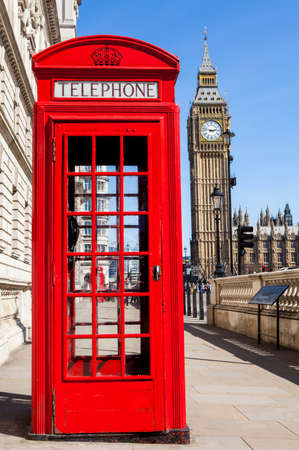 An iconic red Telephone Box with Big Ben in the background in London. 스톡 콘텐츠