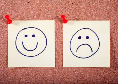 happy face: A Happy and Sad face pinned to a noticeboard. Stock Photo