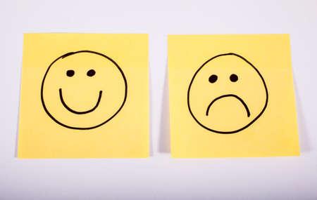 2 枚のメモ紙に幸せと悲しい顔。 写真素材
