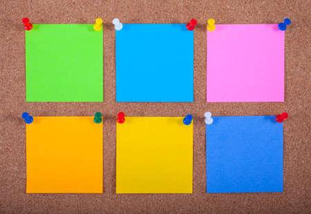 sticky notes: Six blank sticky notes pinned onto a noticeboard.