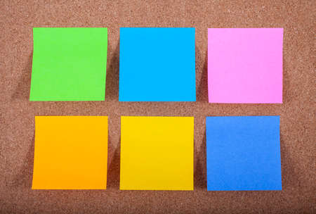 Six blank sticky notes on a noticeboard.
