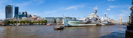 hms: A magnificent panoramic view taking in the sights of the skyscrapers in the City of London, the historic HMS Belfast and Tower Bridge on the River Thames in London.  Canary Wharf can also be seen in the distance. Editorial