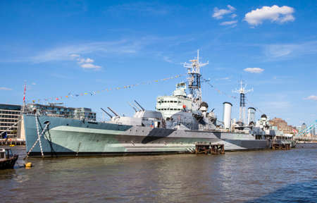 hms: A view of the historic battleship HMS Belfast docked on the River Thames in London.  Canary Wharf can be seen in the distance.