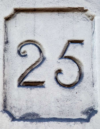 numero: Number 25 engraved on a textured wall.