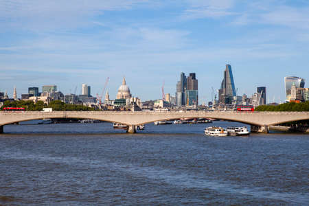 st pauls: A view of Waterloo Bridge and the River Thames along with the dome of St. Pauls Catehdral and skyscrapers in the City of London.