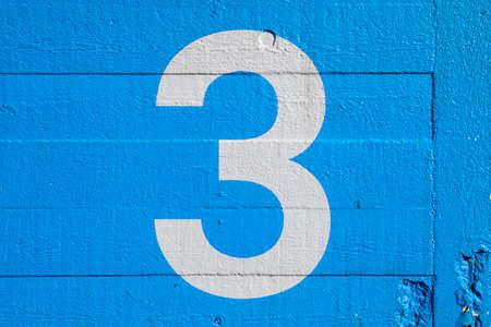 nombres: Le numéro 3 peinte sur un mur bleu. Banque d'images