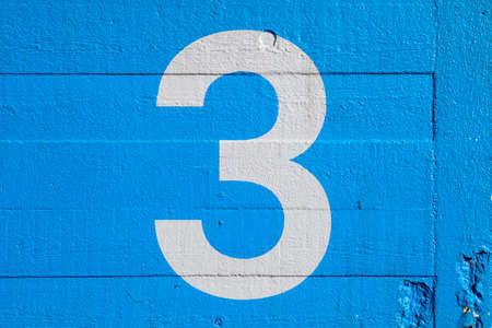 three objects: The Number 3 painted on a blue wall.