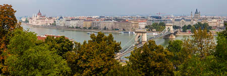 building a chain: A beautiful panoramic view from Castle Hill taking in the sights of the Hungarian Parliament Building, the Chain Bridge, St. Stephens Basilica and the River Danube in Budapest, Hungary.