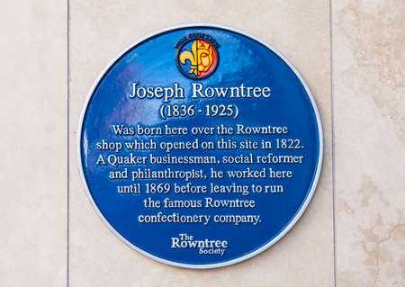 blue plaque: A blue plaque marking the location where, in 1836, Joseph Rowntree was born in York, England.  Joseph Rowntree was the owner of the famous Rowntree Confectionery Company.