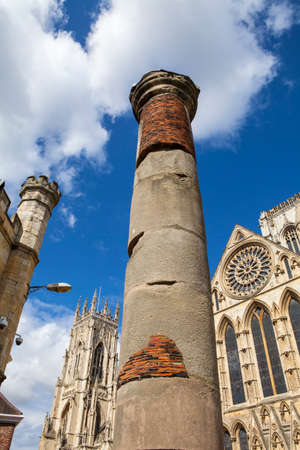 minster: The historic Roman Column with York Minster in the background in York, England. Stock Photo