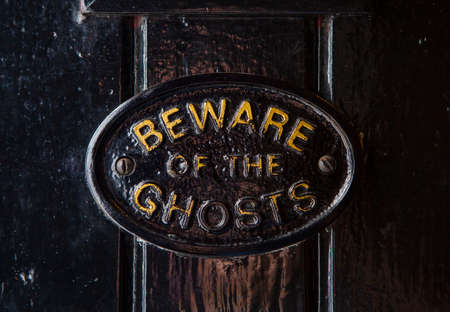 A Beware of the Ghosts plaque on the entrance to the Golden Fleece public house in York, England. It is regarded to be the most haunted pub in York.