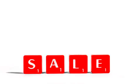 spelt: SALE spelt out with red lettered tiles over a white background. Stock Photo