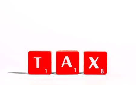 spelt: TAX spelt out with red lettered tiles over a white background. Stock Photo