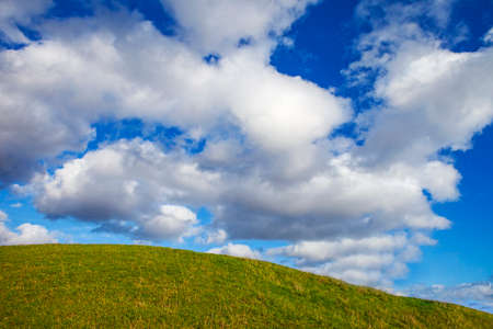 hilltop: Lush green hilltop with a beautiful cloudscape.