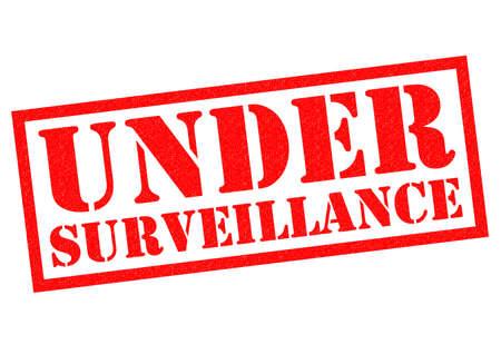 under surveillance: UNDER SURVEILLANCE red Rubber Stamp over a white background.
