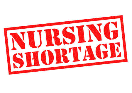 staffing: NURSING SHORTAGE red Rubber Stamp over a white background. Stock Photo