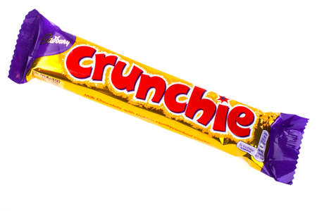 LONDON, UK - JUNE 16TH 2016: An unopened Crunchie chocolate bar manufactured by Cadbury, pictured over a plain white background on 16th June 2016. Editorial