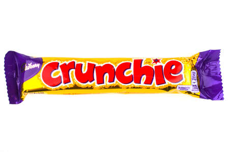 LONDON, UK - JUNE 16TH 2016: An unopened Crunchie chocolate bar manufactured by Cadbury, pictured over a plain white background on 16th June 2016. Sajtókép