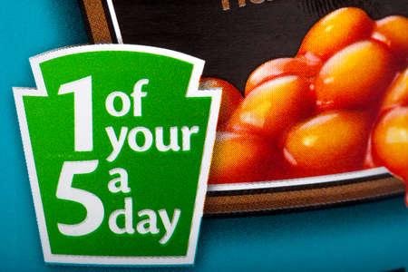 informing: LONDON, UK - MAY 6TH 2016: A close-up of a sign on a can of Heinz Baked Beans informing the consumer that the contents contain 1 of your recommended 5 fruit and vegetable portions a day, on 6th May 2016. Editorial