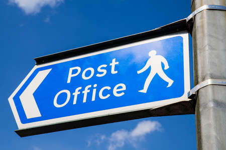 royal mail: A sign showing the direction of the nearest Post Office in an English town.