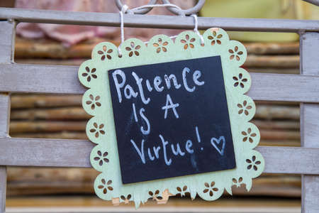 philosophical: A philosophical Patience is a Virtue sign attached to a bench.