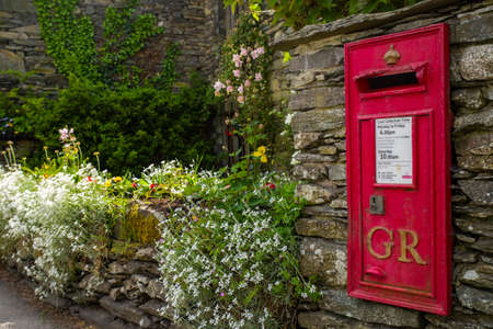post box: An old-fashioned post box in a traditional English countryside village.