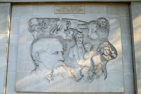 dickens: A Bas Relief Carving on Marylebone Road in London, marking the location where Charles Dickens wrote six of his famous novels. Editorial