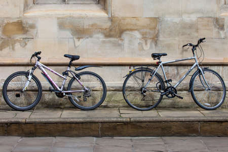 mode transport: CAMBRIDGE, UK - APRIL 8TH 2016: Two bicycles propped up against a wall in the university city of Cambridge in the UK, on 8th April 2016.  Bicycles are the quickest and cheapest mode of transport in and around the town. Editorial